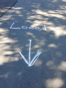 "Spray painted word ""Locate"" on street with arrow pointing to photographer"