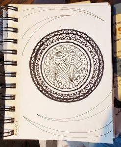 Circular drawing with black pens in a small blank notebook